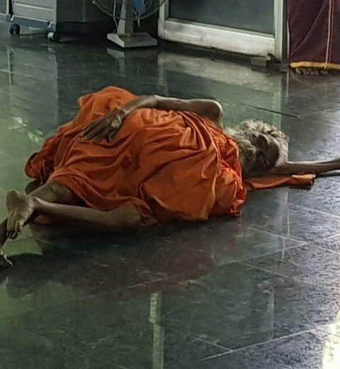 muoku podi swami laying on floor in meditation hall at sheshadri ashram
