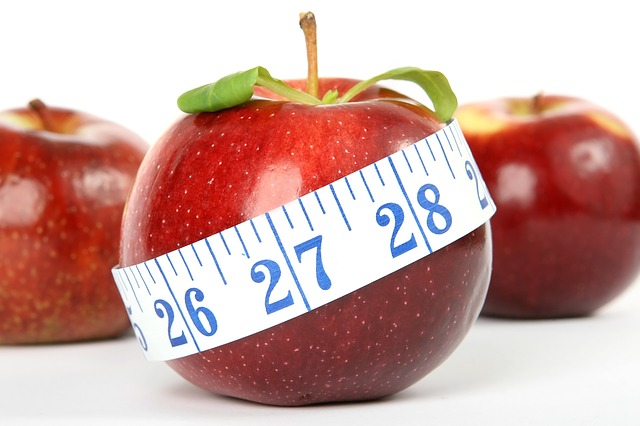 red apples with measuring tape