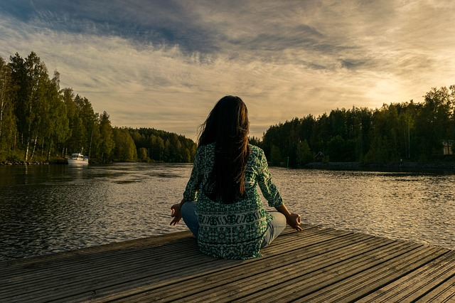 woman in meditation at lake